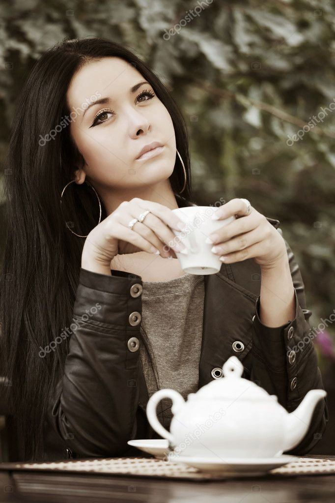 Young woman drinking tea at sidewalk cafe. — Stock Photo #8470593