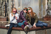 Teenage girls relaxing against a city fountain — Stock fotografie
