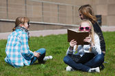 Teenage schoolgirls relaxing on a campus — Stock Photo