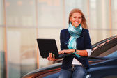 Young businesswoman using laptop against office windows — Stock Photo