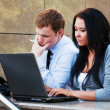 Young business couple using laptop — Stock Photo