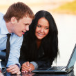 Young business couple using laptop — Stock Photo #9848242