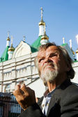 Homeless senior against a cathedral — Stock Photo