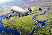 Avião moderno no céu perto de aeroporto. — Fotografia Stock