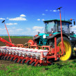 Tractor plowing the fields in early spring. - Stock Photo