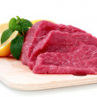 Beef steak  on meat hardboard with green leaf and lemon. — Stock Photo