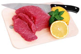Cut of beef steak , knife with lemon slice. — Stok fotoğraf