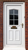 White front door in a red brick building — Stock Photo