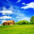 House and green field on blue sky - Stok fotoğraf