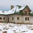 House under construction in winter scenery - Stock Photo