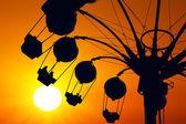 Amusement ride on golden sunset — Stock Photo