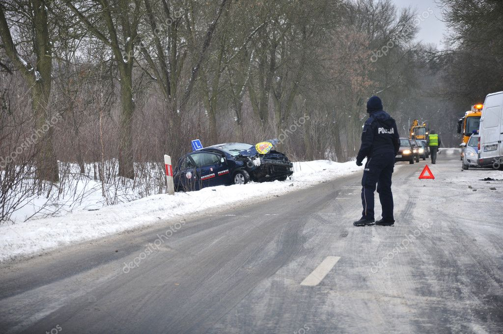 Accident on an icy road. Driving Schools in the ditch - policeman directs traffic  Stock Photo #8528156