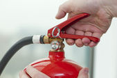 Hand presses the trigger fire extinguisher — Стоковое фото