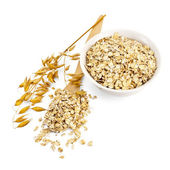 Rolled oats in a bowl and spoon — Stock Photo