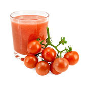 Juice tomato in a glass and a bunch of tomatoes — Stock Photo