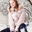 Beautiful young girl in a hood on a background a snow-bound tree - Stock Photo