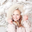 Beautiful young girl in a hood on a background a snow-bound tree — Stock Photo