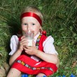 Little girl with milk glass on hay — Stock Photo #8981560
