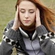 Sad girl with headphones sitting at spring meadow. — Stock Photo