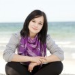 Funny teen girl sitting on the sand at the beach. — Stock Photo #10287478