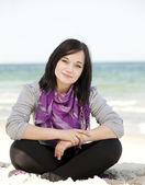 Divertente ragazza adolescente seduto sulla sabbia in spiaggia. — Foto Stock