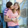 Young couple kissing near graffiti background. - Stock Photo
