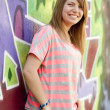 Style teen girl near graffiti wall. - Stock Photo