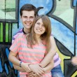 Young couple near graffiti background. — Stockfoto