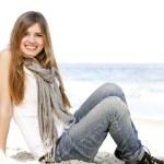 Funny teen girl sitting near the sea. — Stock Photo