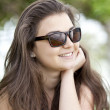 Stock Photo: Brunette girl in sunglasses at the summer park.