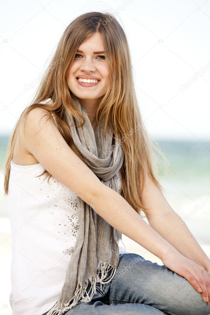 Funny teen girl sitting near the sea.  Stock Photo #10449293