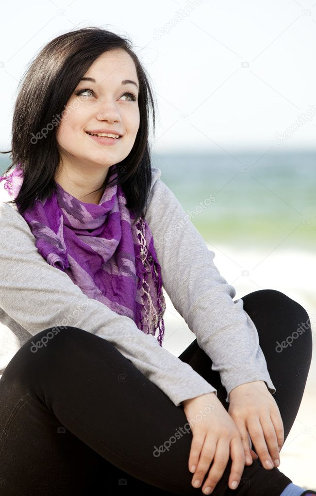 Funny teen girl sitting on the sand at the beach.  Stock Photo #10449298