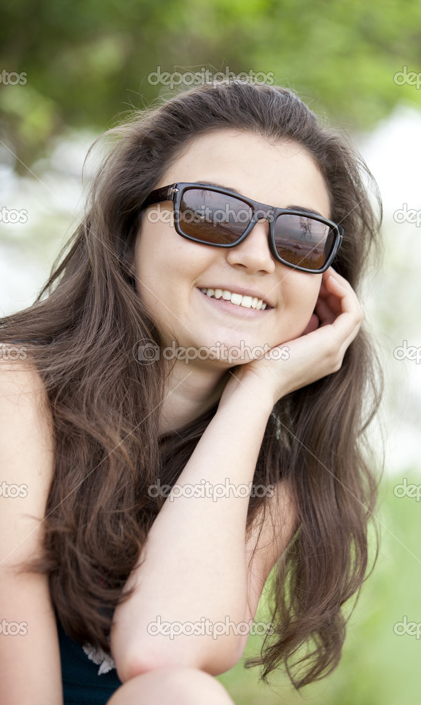 Brunette girl in sunglasses at the summer park.  Stock Photo #10449336