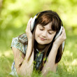 Young fashion girl with headphones at green spring grass. — Stock Photo #10549288
