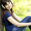 Young fashion girl with headphones at green spring grass. — Stock Photo #10549299