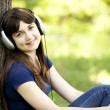 Young fashion girl with headphones at green spring grass. — Stock Photo #10549302