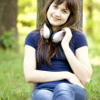 Young fashion girl with headphones at green spring grass. — Stock Photo #10549320