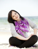 Grappig tiener meisje, zittend op het zand op het strand. — Stockfoto