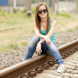 Young girl in glasses sitting at railway. — Stock Photo