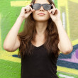 Style teen girl in sunglasses near graffiti background. — Stock Photo #10626074