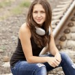 Stock Photo: Teen girl with headphones at railways.
