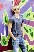 Style teen boy with in sunglasses near graffiti background. — Stock Photo