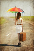 Lonely girl with suitcase and umrella at country road. — Stock Photo