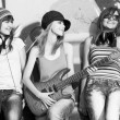 Three beautiful girls with guitar and graffiti wall at backgroun — Stock Photo #7980483