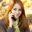 Red-haired girl calling by the phone in the autumn park. — Stock Photo