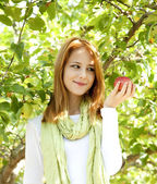 Beautiful young redhead woman standing near the apple tree. — Stock Photo