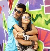 Młoda para w pobliżu graffiti tło. — Zdjęcie stockowe