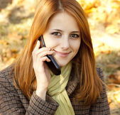 Roodharige meisje bellen door de telefoon in de herfst park. — Stockfoto
