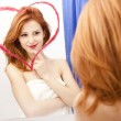 Redhead girl near mirror with heart at it in bathroom. - Stock Photo