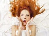 Verrast roodharige meisje in bed. studio opname. — Stok fotoğraf